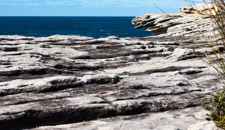 Oceanside rocky cliff top sandstone wave ridges with blue coastal sea and sky in background