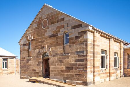 Sandstone brick convict built building with decorative stonework and doorway set in pebbled courtyard against clear blue sky