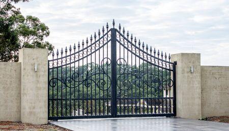 Black metal wrought iron driveway property entrance gates set in concrete brick fence, lights, garden trees in background 版權商用圖片