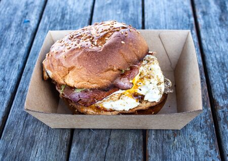 Egg, bacon breakfast roll in takeaway box set on wooden tabletop Banque d'images - 132087093