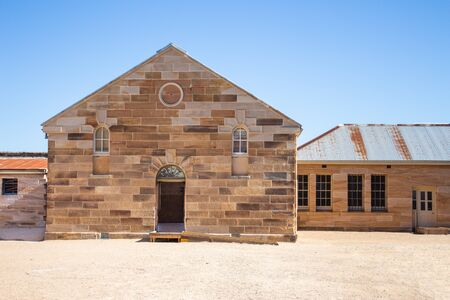 Sandstone brick convict built building with decorative stonework, corrugated iron roof, arched doorway, pebbled courtyard against clear blue sky