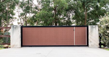 Black brown metal wrought iron driveway property entrance gates set in concrete brick fence, lights, eucalyptus garden trees in background