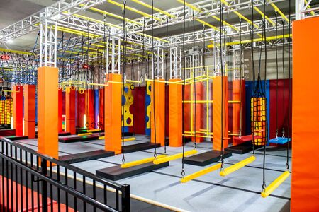 Brightly coloured interior ninja warrior parkour gym obstacle course with aerial netting Imagens