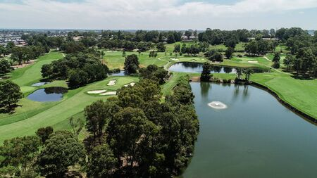Aerial drone view Golf course fairway, water hazards, fountain, green with sand bunkers surrounded by trees