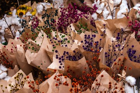 Fresh cut bunches of purple, orange, yellow, green, pink flowers wrapped for sale