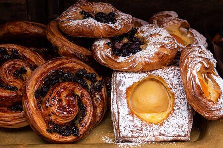 Freshly baked danish pastries, custard, apricots, raisins, cinnamon swirl dusted in icing sugar and glaze Standard-Bild