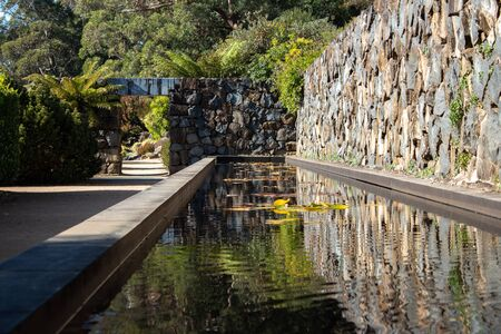 Garden water pond feature with rock feature wall, water lilies, arch doorway along stone walkway surrounded by trees