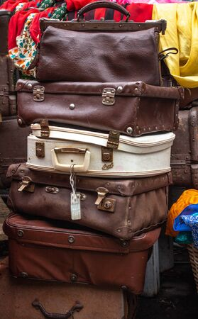 Tower of old brown leather suitcases, travel bags squashed onto of each other