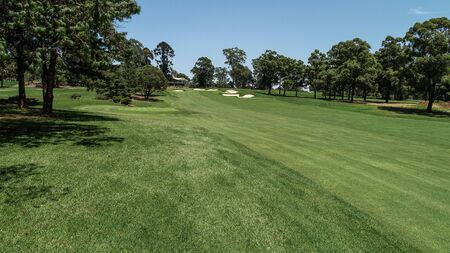 Golf course fairway, sand bunkers, lush green grass surrounded by trees against blue sky