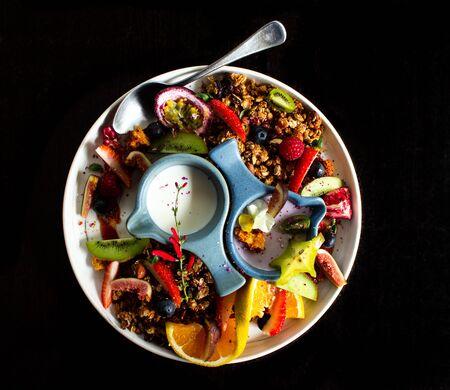 Granola muesli breakfast served with fresh fruit, milk, yoghurt, strawberries, passionfruit, orange, kiwifruit, fig Standard-Bild