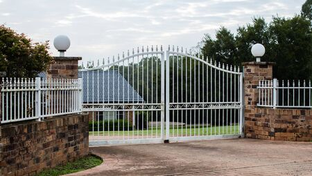 White metal wrought iron driveway property entrance gates set in brick fence, garden trees in background Standard-Bild