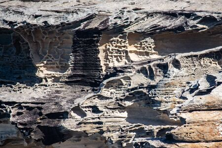 Sandstone cliff rock face layers weathered by seaside, ideal as natural geologic background