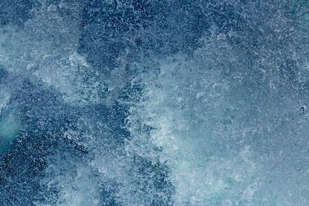 Aquatic background of sea surf waves splashing close up with clear blue green water and white foam