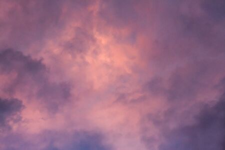 Pink, purple, orange golden glow of clouds at sunset against blue sky ideal as nature background Standard-Bild