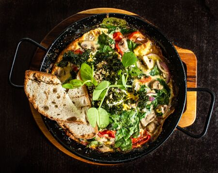 Spanish omelette breakfast served hot in pan with spinach, mushrooms, tomatoes, cheese, bread Standard-Bild