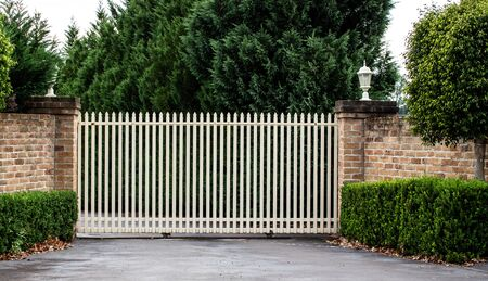 Metal wrought iron driveway property entrance gates set in brick fence, garden trees in background Standard-Bild
