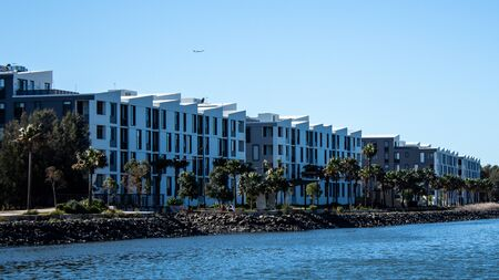 Waterfront apartment condominiums in suburban community on riverbank  with tree lined walkway, blue sky in background