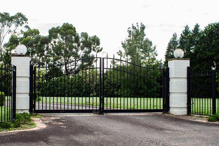 Black metal wrought iron driveway property entrance gates  set in brick fence, lights, green grass, garden trees Standard-Bild