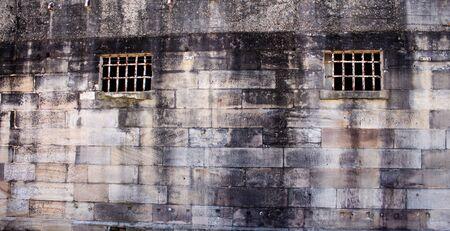 Historical sandstone convict built brick prison building, windows rusting security grill, wall background Standard-Bild