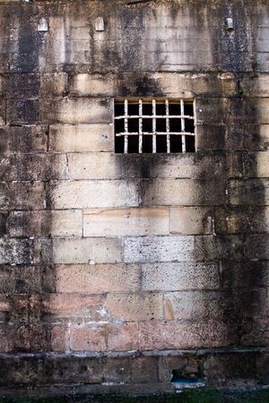 Historical sandstone convict built brick prison building, windows rusting security grill, wall background Stock Photo