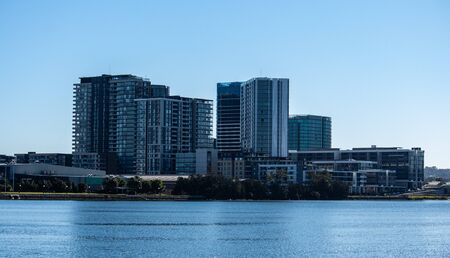 Urban high rise apartment condominiums community set on riverbank against blue sky