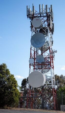 Communications radio tower with satellite dish mobile cell phone against blue sky