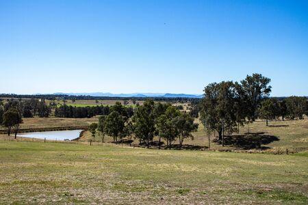 Rural Australian farmland with water dam, fences, hilltops, eucalyptus gum trees, blue sky Standard-Bild