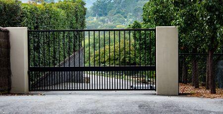 Black metal wrought iron driveway property entrance gates set in brick fence, concrete path, garden trees Standard-Bild