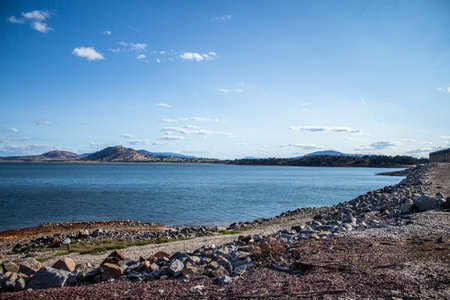 Blue water filled lake dam with rocky foreshore and small hills in background against blue sky