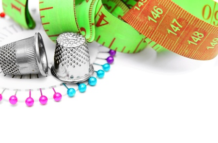 Measuring roulette, needles and thimbles  On a white background  photo