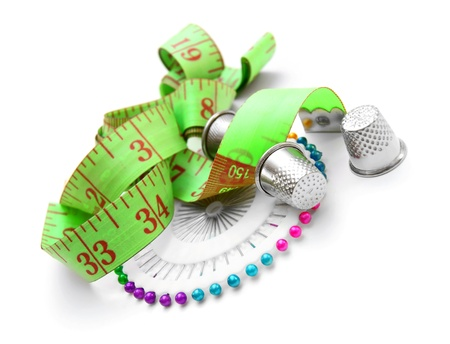 Needles, thimbles and a measuring roulette  On a white background  Stock Photo