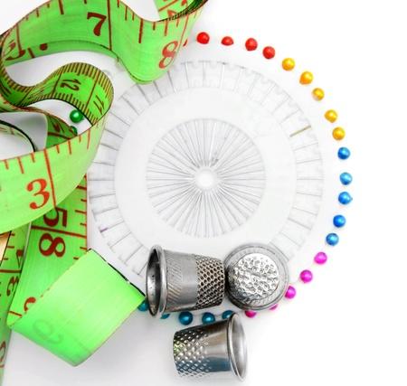 바늘, 골무 및 흰색 배경에 측정 테이프