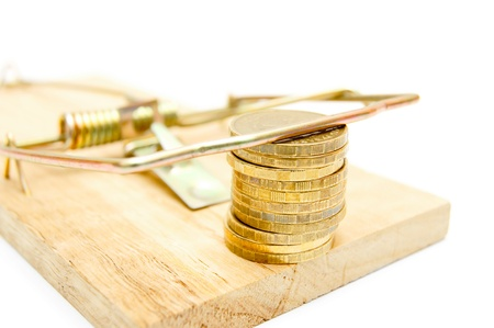 Gold coins in a mousetrap  On a white background  photo