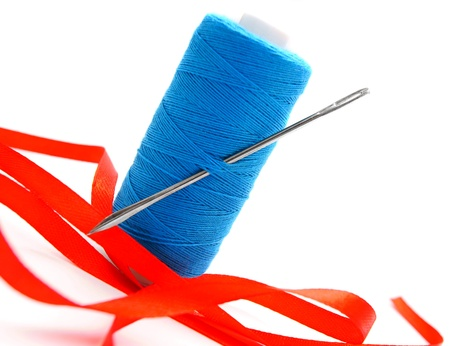 satiny: Threads, a needle and a satiny tape  On a white background  Stock Photo