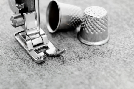 The sewing machine and thimbles  On a fabric  photo
