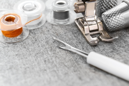 The sewing machine, threads and thimbles on a fabric  photo