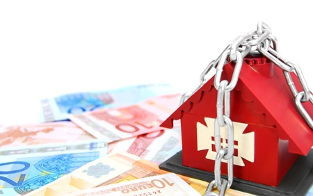 dwelling mound: Money, chain and the toy house  On a white background  Stock Photo