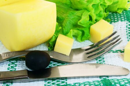 Cheese, greens, olive on a towel. photo
