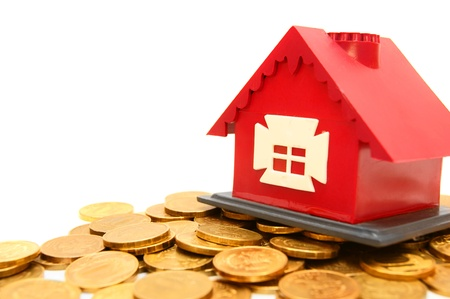 The toy house on gold coins  On a white background  photo