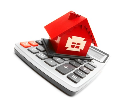 home finance: The toy house and the calculator. On a white background.