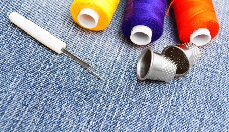 Threads and thimbles on jeans . photo