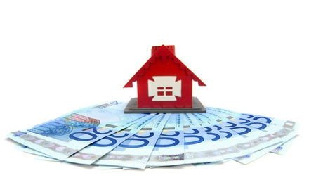 dwelling mound: The toy house and money. On a white background. Stock Photo