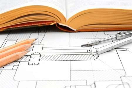 The book, pencils and compasses on the drawing. Stock Photo