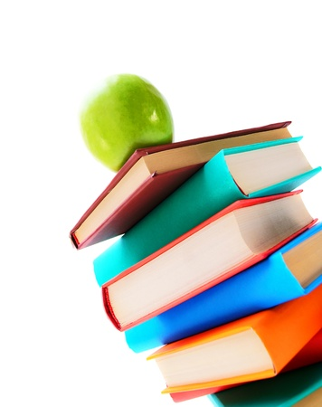 Books and a green apple. On a white background. photo