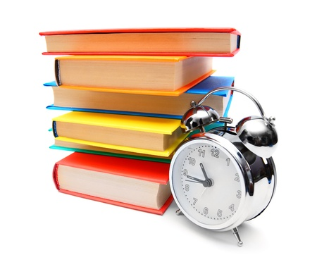 Multi-coloured books and alarm clock. On a white background. photo