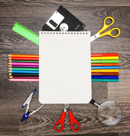 Notebook and school tools. On a wooden background. photo
