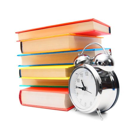 morning blue hour: Multi-coloured books and alarm clock  Stock Photo