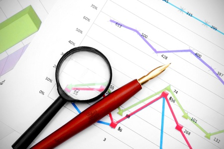 enlarger: Magnifier and pen on financial graphs  Stock Photo