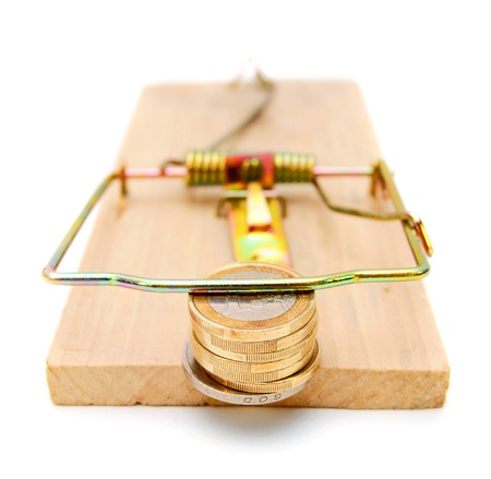 Coins in a mousetrap. On a white background. photo