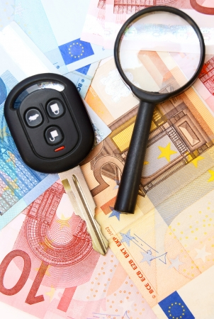 Key from the car and a magnifier. On money, euro. Stock Photo - 17237115